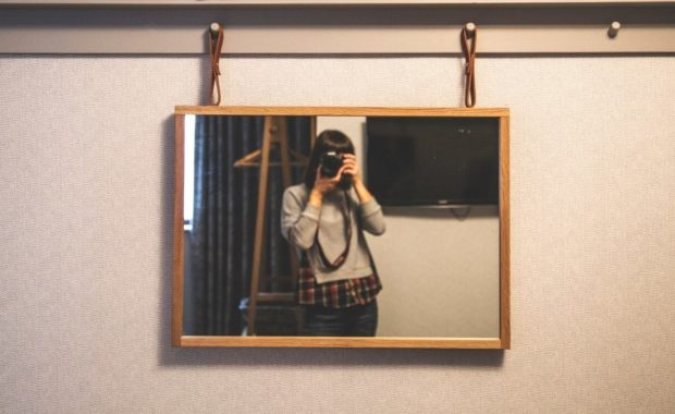 Person taking picture of mirror